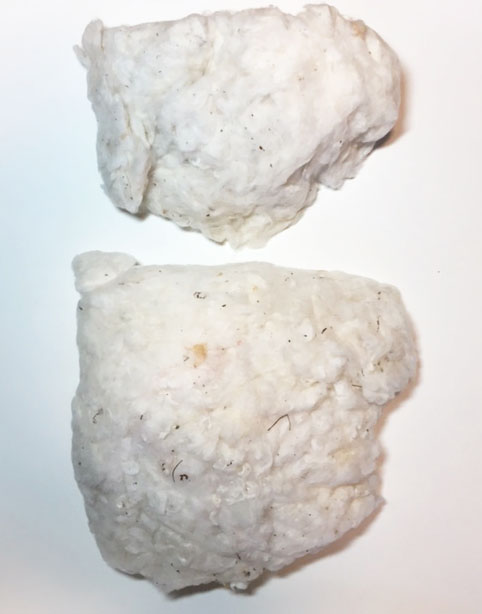 Two 10 oz. lumps of cotton. The top lump has not been bowed while the bottom lump has. Bowing helps create uniform air pockets throughout the lump and provide improved fluffiness.
