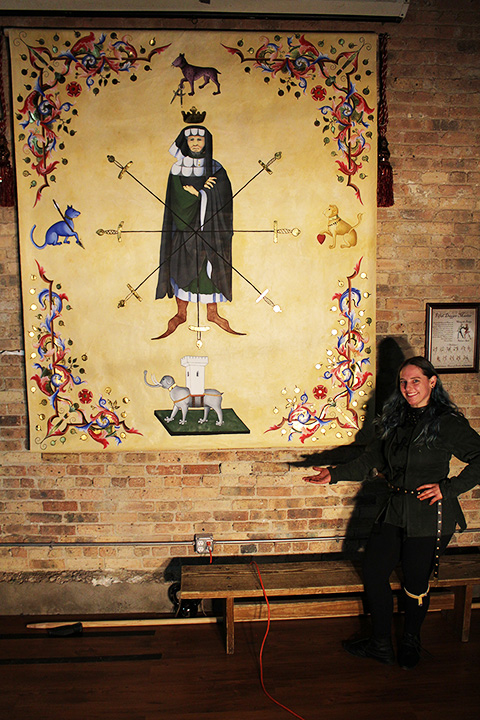 Erin Fitzgerald, Free Scholar of the Chicago Swordplay Guild, with her full-color Segno della Spada. It hangs in the center of the longest wall in the training salle.