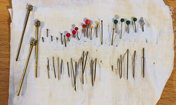 My brass pin collection. Much used and abused through the years and yet still insufficient to the task at hand. I could only use the butch ones on the left for the braid pinning. I got away with using the thin ones when securing the braids to the back of her head, but it was iffy.