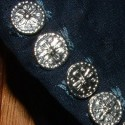 Close-up of pewter buttons and boxy buttonholes